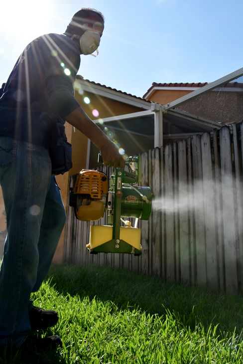 A Miami-Dade County mosquito inspector sprays for mosquitoes.