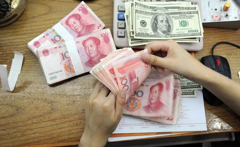 A Chinese bank worker counts 100-yuan notes and US dollar bills at a bank counter in Hefei, east China's Anhui province.