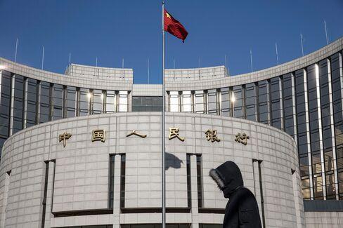 Pedestrians walk past the People's Bank of China in Beijing.