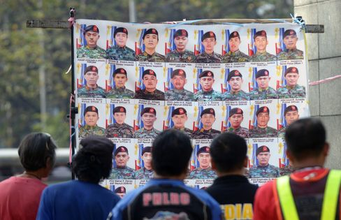 People look at photos of elite commandos who died in a police raid in the southern province of Mindanao last year.