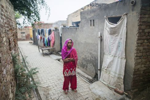 Kamlesh stands next to a community toilet in Lahli village