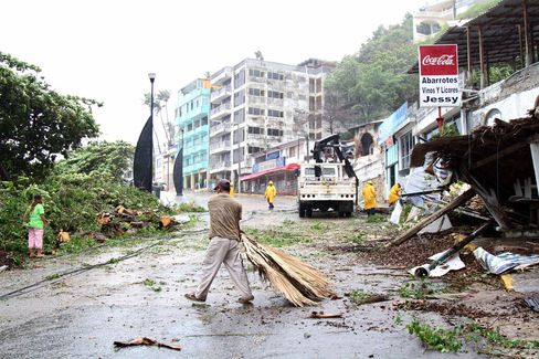 A man clears debris caused by wind and rain in the Pacific resort city of Acapulco, Mexico, on June 14, 2015.