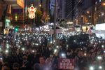 Demonstrators hold signs and shine lights from smartphones during a protest in Wan Chai district of Hong Kong.