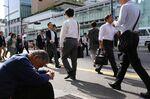 Morning commuters walk past a man sitting outside Shinjuku Station in Tokyo.