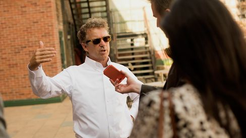 Senator Rand Paul speaks to a local radio reporter during a campaign event in Muscatine, Iowa, on May 28, 2015.