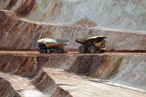 Dump trucks drive along a haul road in the open pit mine at Norton Gold Fields Ltd. Enterprise operations 68 kilometers north-west of Kalgoorlie, Australia, on Tuesday, Aug. 4, 2015. Norton Gold Fields is controlled by China's Zijin Mining Group, the world's biggest gold producer by market value.