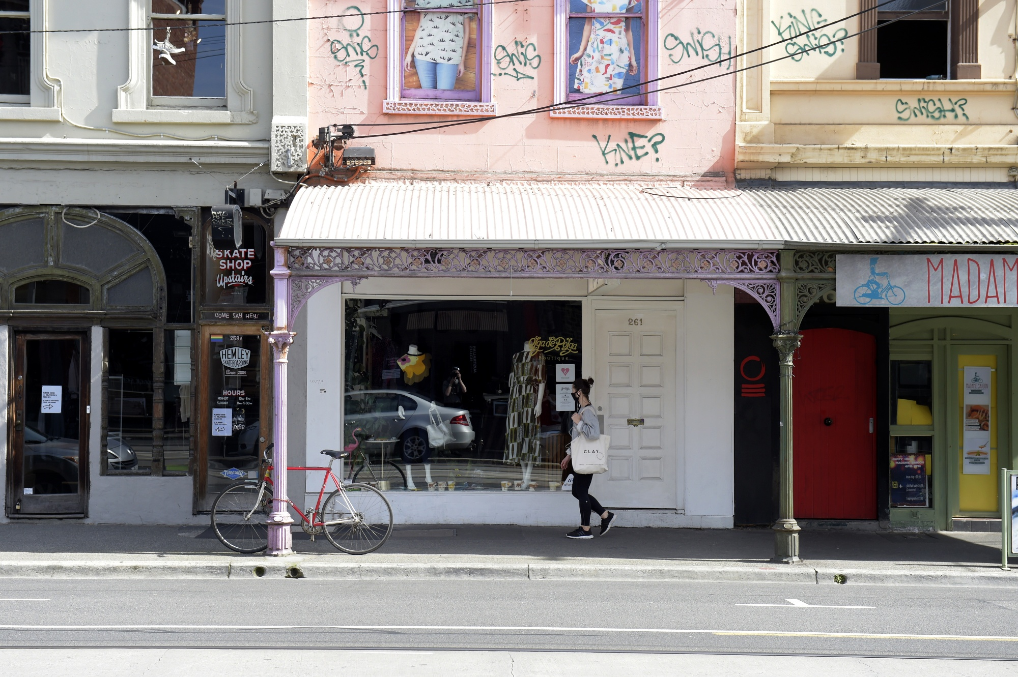 A pedestrian wearing a protective mask walks past a closed store in Melbourne, on Sept. 1.