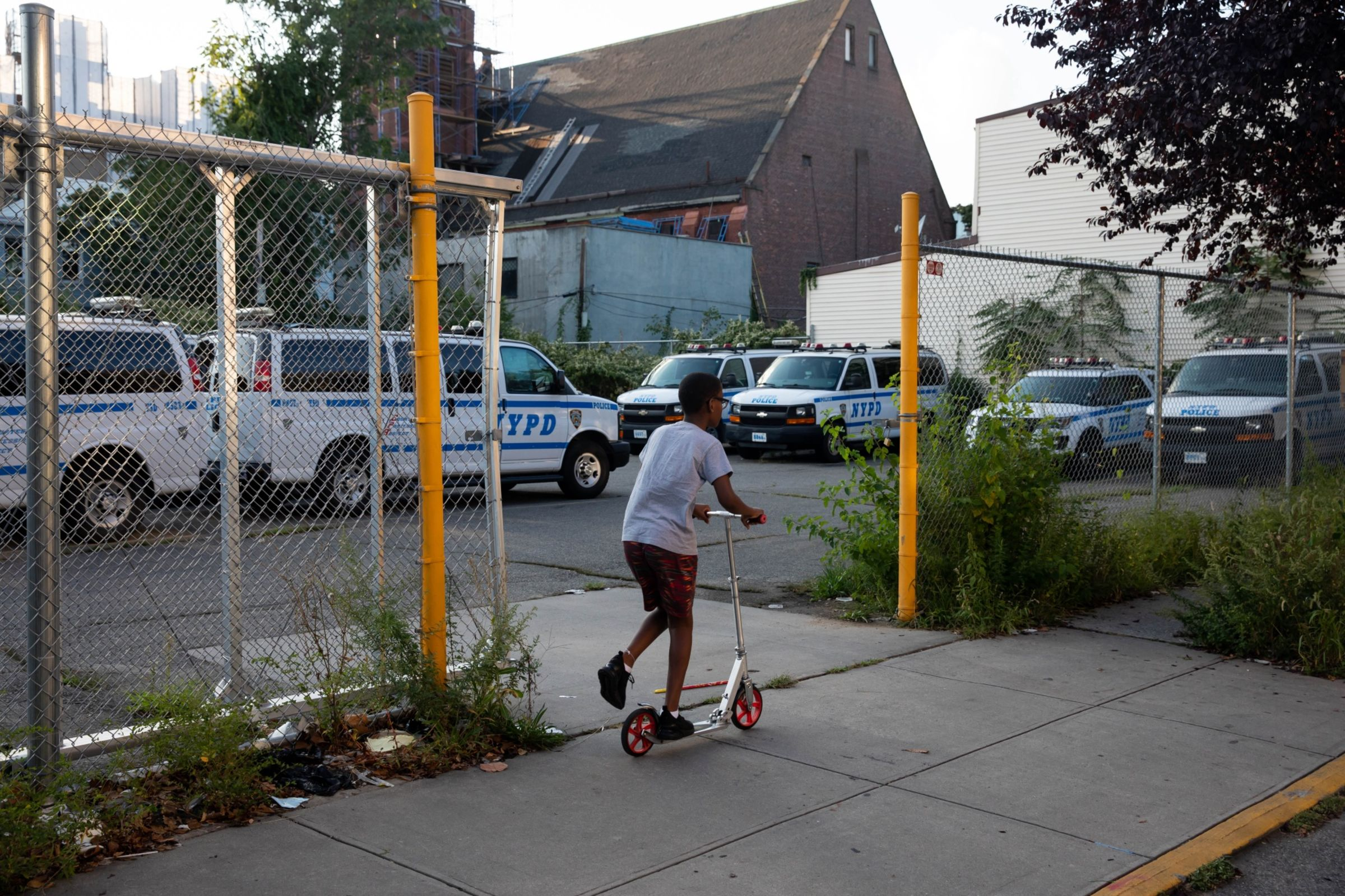 A child rides a scooter past an NYPD lot in the 75th precinct.