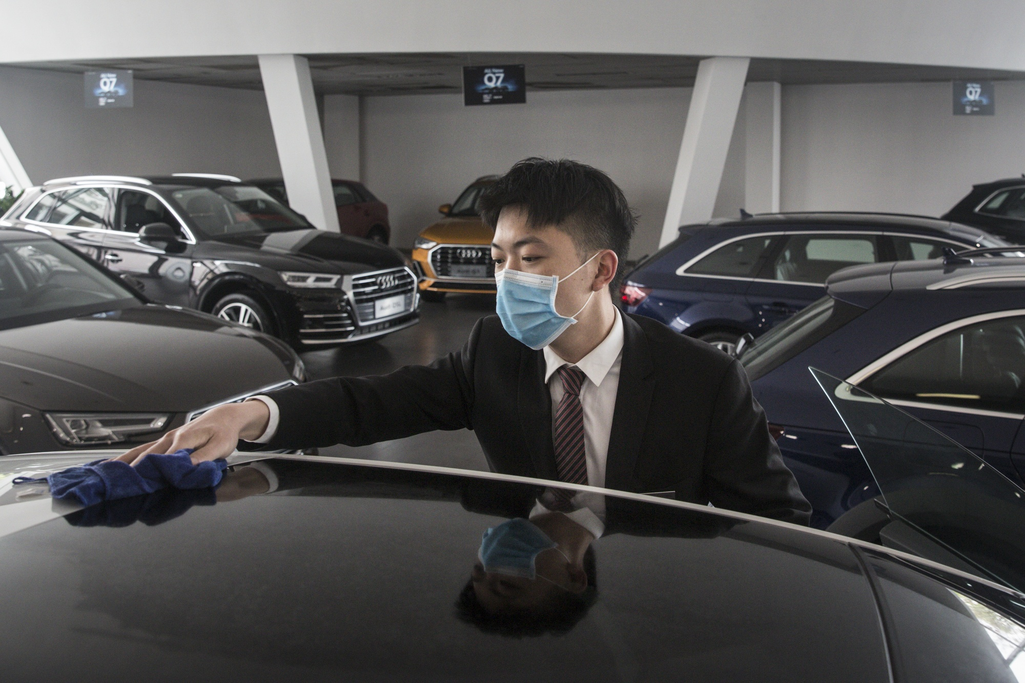 An employee wearing a protective mask wipes a vehicle on display inside an Audi AG dealership in Wuhan.