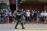 A riot police officer points a tear gas rifle towards demonstrators in Hong Kong, on July 1.