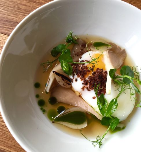 A poached egg with pea shoots and mushroom broth.
