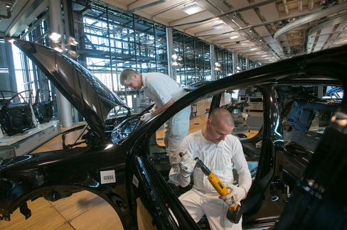 Employees assemble the body shell of a Volkswagen Phaeton automobile on the production line at the Volkswagen AG factory in Dresden, Germany.