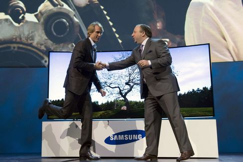 Michael Bay, left, greets Joe Stinziano, executive vice president of Samsung Electronics America, during a press conference at CES 2014.