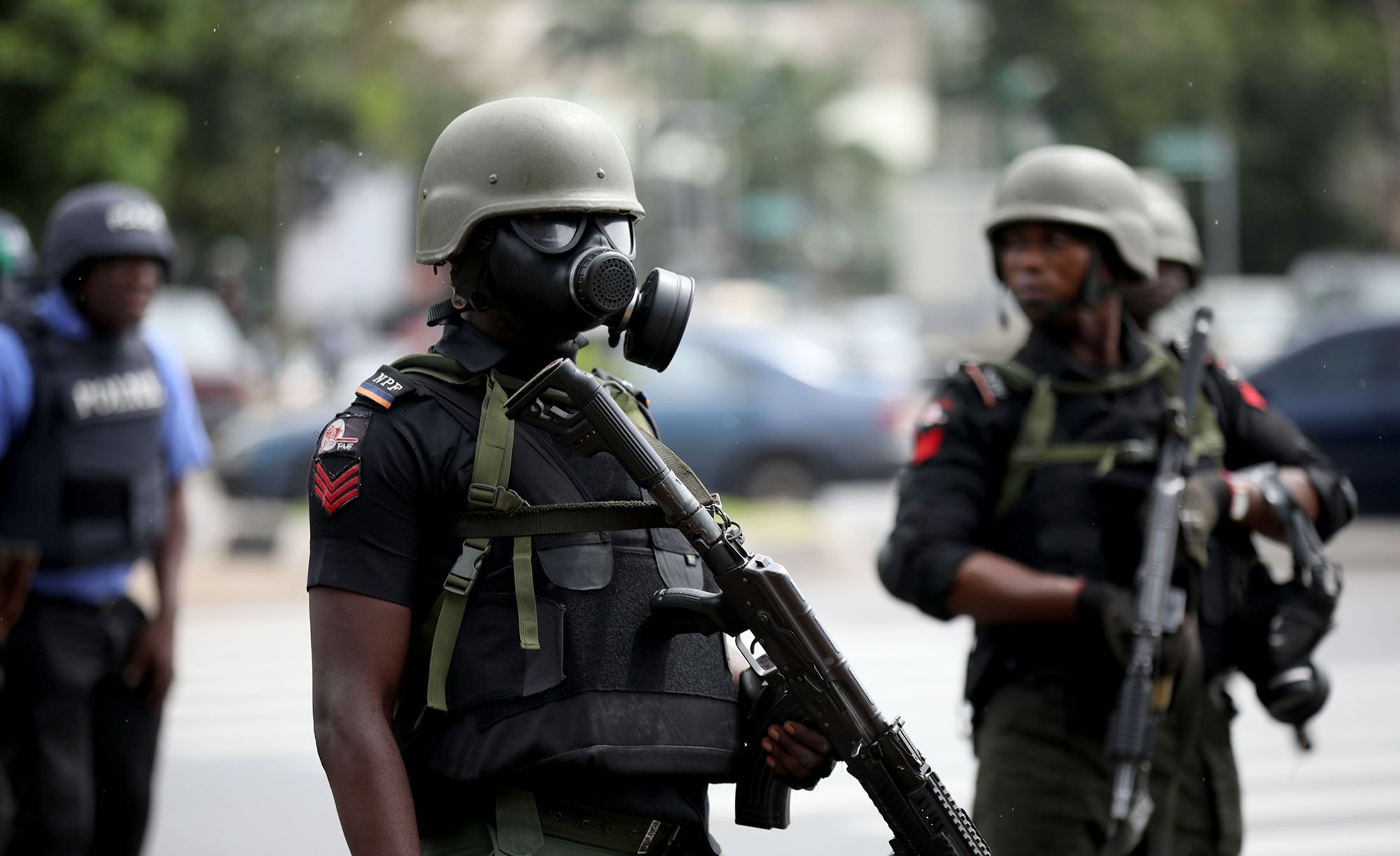 Riot policemen wearing masks stand in a street during aprotest in Abuja on July 23, 2019.