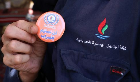 """A Kuwaiti oil worker from the state oil company shows a badge reading in Arabic: """"the strike will not compromise."""""""
