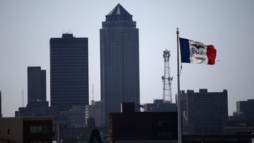 The Iowa state flag flies in front of the Des Moines skyline on April 11, 2015.