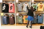 An employee arranges t-shirts displayed at Fast Retailing Co.\'s Uniqlo store in the Ginza district of Tokyo, Japan, on Wednesday, April 10, 2013. Fast Retailing, Asia's largest apparel retailer, is scheduled to announce earnings tomorrow.