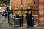 A police officer stands next to a public litter bin next to a supported housing project in Salisbury.