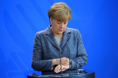 Angela Merkel, Germany's chancellor, looks at her wristwatch during a news conference at the Chancellery in Berlin, Germany, on Monday, Sept. 7, 2015.