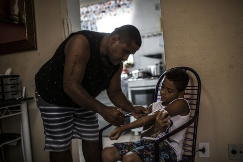 Rodrigo Batista da Silva administers state-issued medicine to his 9-year-old son.
