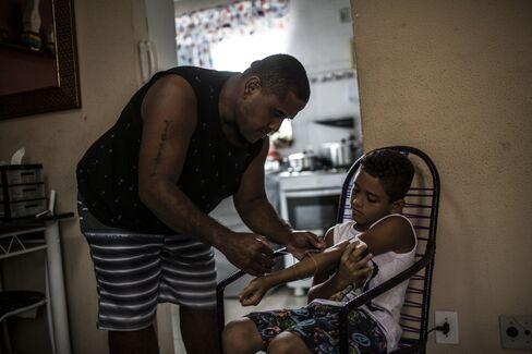 Rodrigo Batista da Silva administers state-issued medicine to his 9-year-old son.