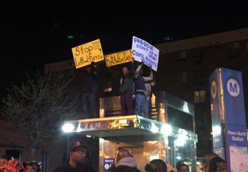 Protesters wait past the 10 p.m. curfew in Baltimore, next to the CVS vandalized in Monday's riots.