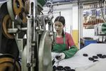 A workers handles a caster wheel at a factory operated in Foshan, China.