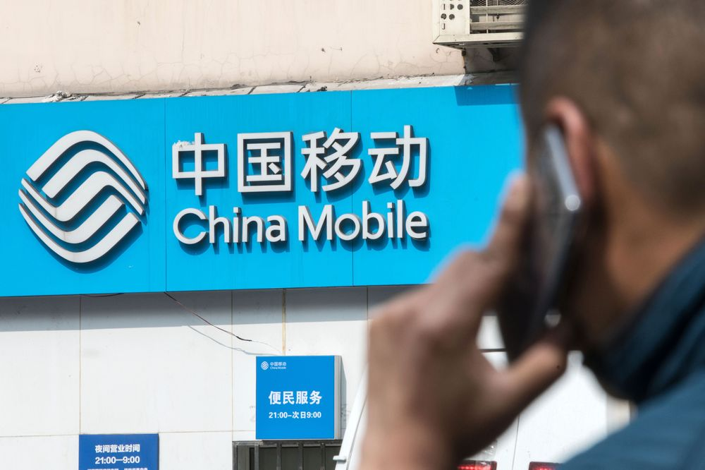 Signage for China Mobile Ltd. is displayed outside a store in Shanghai.