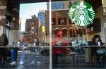 Customers sit inside a Starbucks corp. location in New York.
