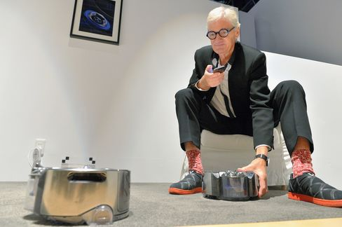 Dyson company founder and chairman James Dyson with the 'Dyson 360 Eye', robot vacuum cleaner in Tokyo.
