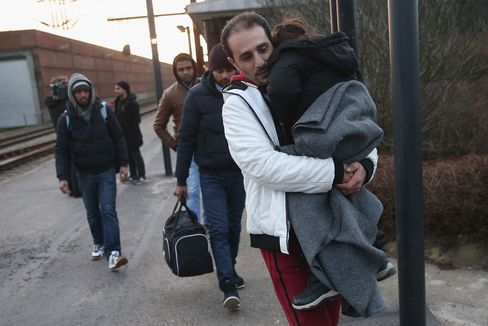 Migrants, many of them from Syria, walk to police vans after police found them while checking the identity papers of passengers on a train arriving from Germany on Jan. 6, in Padborg, Denmark.