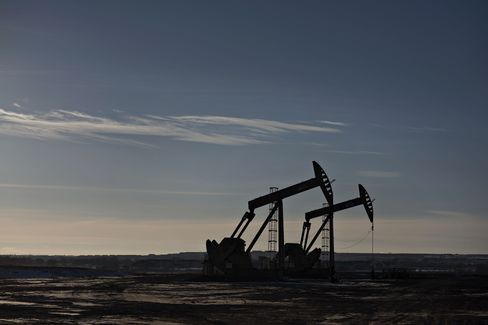 Pumpjacks stand on the site of an oil well outside Williston, North Dakota, U.S., on Wednesday, Feb. 11, 2015.