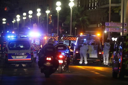 Police officers and rescue workers arrive at the scene of an attack on July 14, after a van plowed into a crowd leaving a fireworks display in the French Riviera town of Nice.
