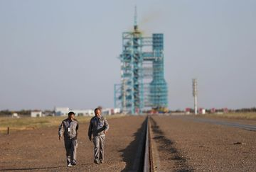 epa05587719 Chinese staff members walk in front of the Long March 2F carrier rocket carrying the Shenzhou-11 spacecraft ahead of its launch at the Jiuquan Satellite Launch Center in Jiuquan in Gansu province, China, 16 October 2016. China will launch Shenzhou-11 spacecraft carrying two crew members into orbit to dock with the Tiangong-2 space lab on a 30-day mission on 17 October 2016.  EPA/HOW HWEE YOUNG
