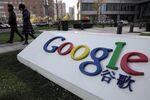Pedestrians walk past the Google Inc. logo in Beijing.