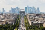 The Arc De Triomphe stands while automobiles travel on the Avenue des Champs-Elysees as skyscrapers sit on the city skyline in the La Defense business district in Paris, France.