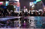 People walk along a street as rain falls in the Shibuya district in Tokyo.