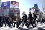 Pedestrians cross an intersection in the Shibuya district of Tokyo.