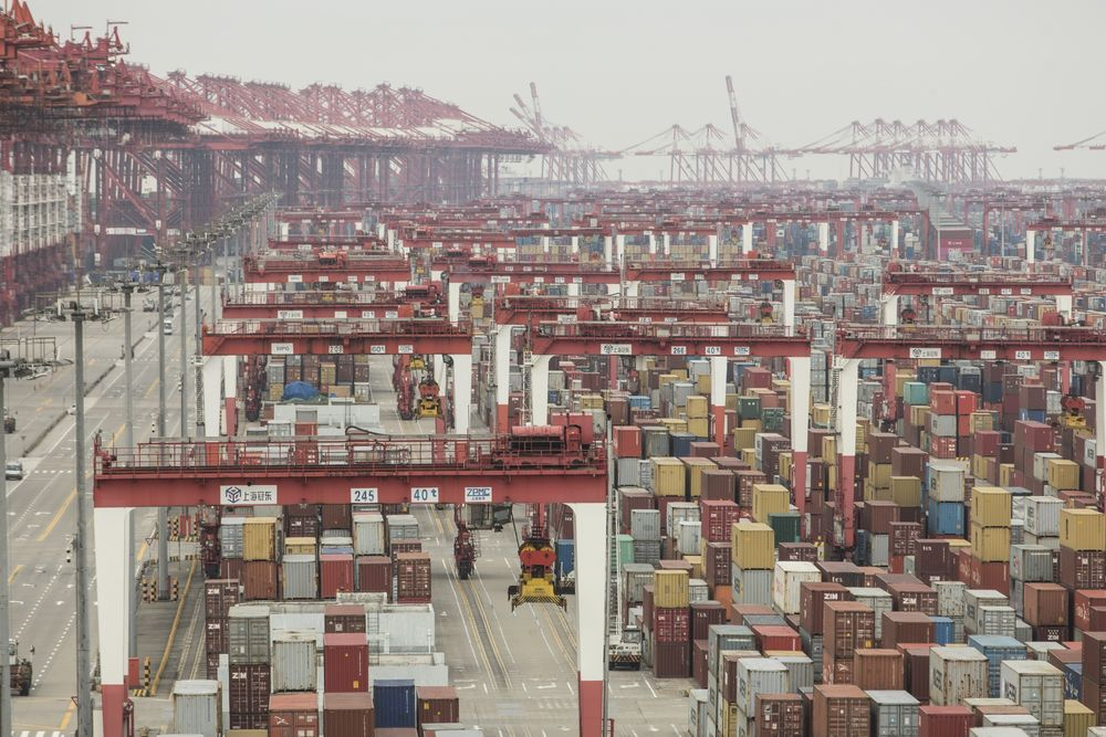Shipping containers next to gantry cranes at the Yangshan Deep Water Port in Shanghai on Feb. 4. Photographer: Qilai Shen/Bloomberg