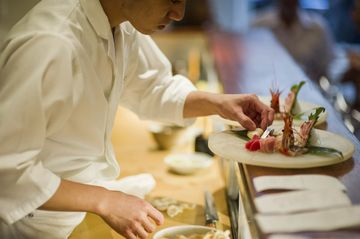 A chef prepares sashimi before it heads to the dining room at 15 East.