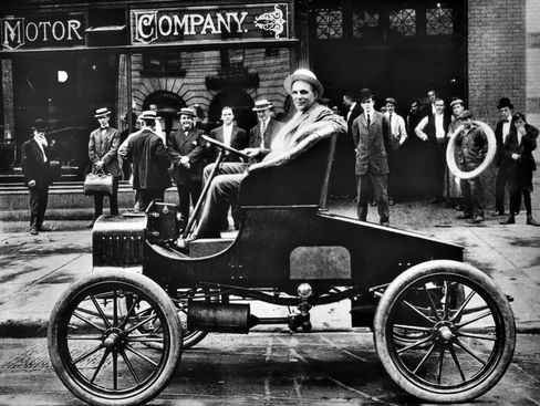 Henry Ford, 37, poses for a photograph in his new Ford ModelTin front of his car plant in Detroit in 1900.