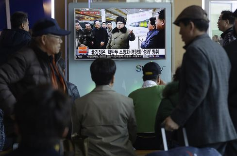 People watch a TV news program showing North Korean leader Kim Jong Un in Seoul on Wednesday. The North Korean leader has said that his country would retaliate with nuclear missiles if it is attacked by the U.S. and South Korea.