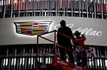 A worker wipes the logo of the General Motors Co. (GM) Cadillac brand display.