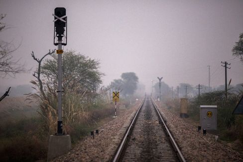 Rail tracks pass through a clearing where villagers go to defecate