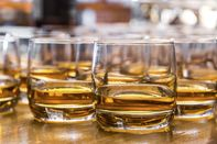 Glasses are filled with whiskey on the table