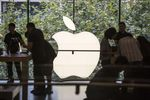 Customers look at products as an Apple Inc. logo.