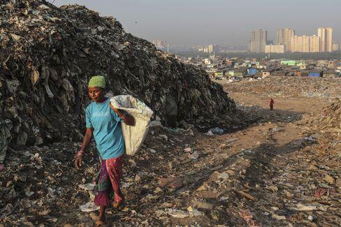A waste-picker walks through the Deonar landfill site in Mumbai. Photographer: Dhiraj Singh/Bloomberg