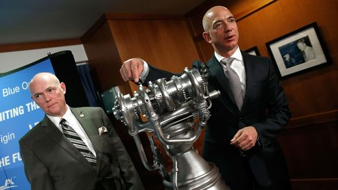 Jeff Bezos (R), the founder of Blue Origin and Amazon.com, gestures toward a model of the new BE-4 rocket engine during a press conference with Tory Bruno (L), CEO of United Launch Alliance, at the National Press Club September 17, 2014 in Washington, DC.