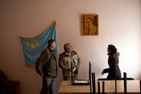 Crimean Tatars at the town council in Bakhchysarai, Crimea, gaze up at a portrait of historical leader Noman Çelebicihan, who presided over the short-lived independent Crimean People's Republic until he was killed by Bolsheviks in 1918