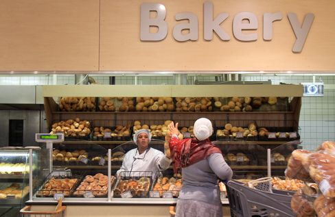 An Employee Passes Bread Rolls to a Customer in Johannesburg